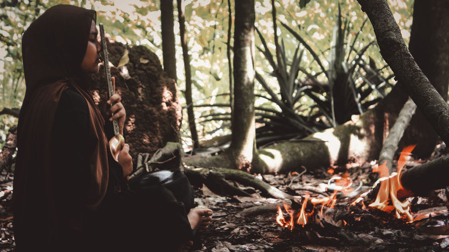 Rear view of woman relaxing in forest