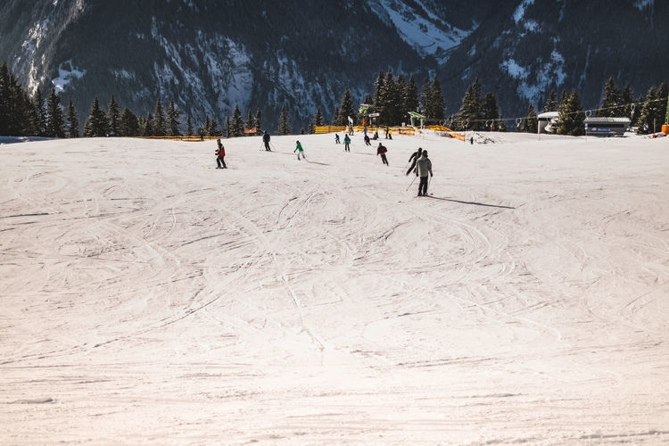 People Skiing On Snow Covered Against Mountain