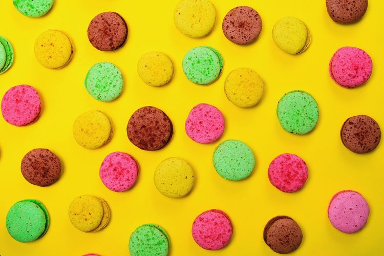 High angle view of colorful macaroons on yellow background