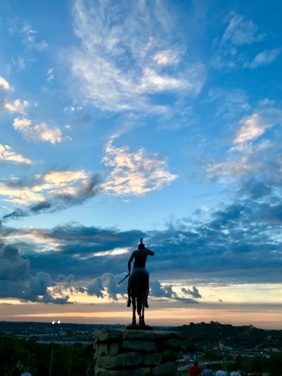 Silhouette statue against sky during sunset