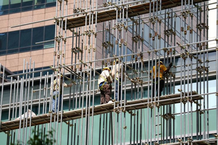 Low angle view of men working on building