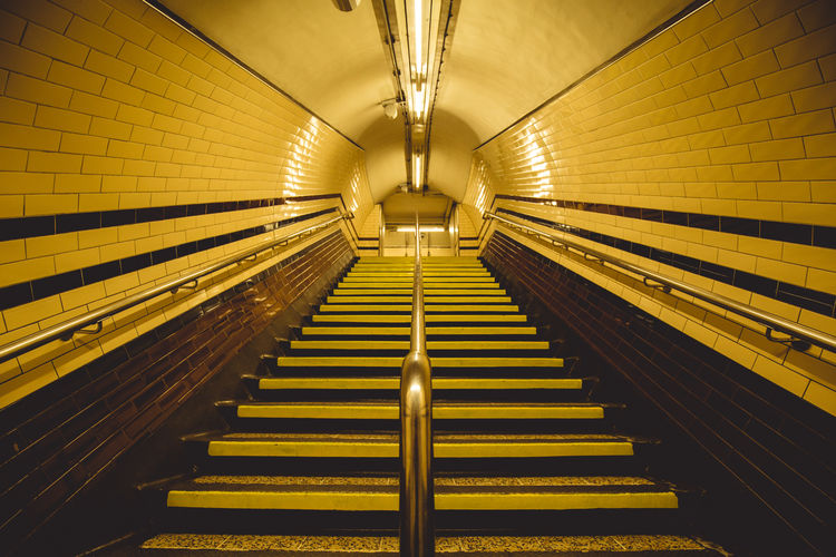 Low Angle View Of Steps At Illuminated Subway Station