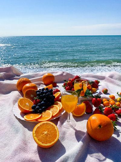 Orange fruits on beach by sea against sky