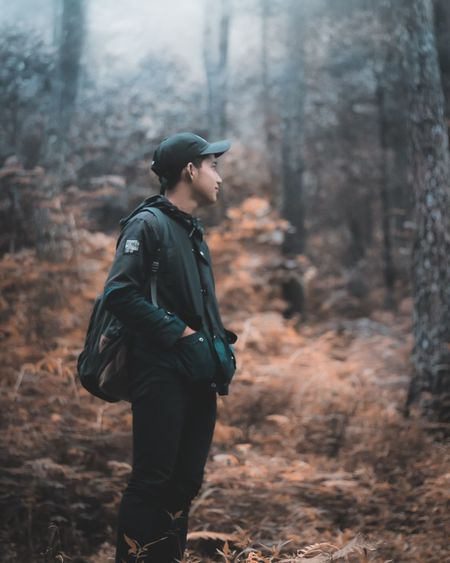 Side view of man looking away in forest