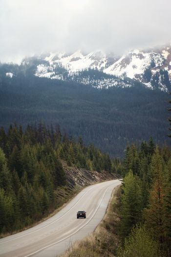 Car on road amidst trees and mountains against sky