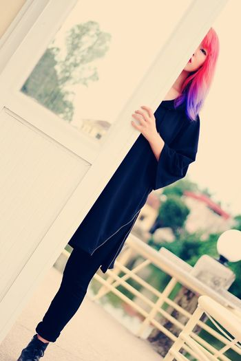 Low angle view of young woman with dyed hair standing by door against clear sky