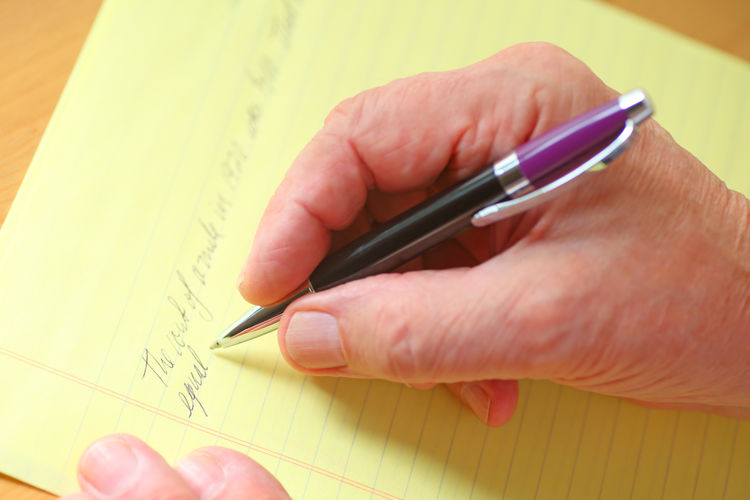 Overhead of man writing in longhand Hands Man Adult Close-up Communication Cursive Writing Day Fingers Handwriting  Holding Indoors  Indoors  Older Person One Person Paper Pen Point Of View Real People Ruled Paper Studio Shot Text Writing Yellow Pad