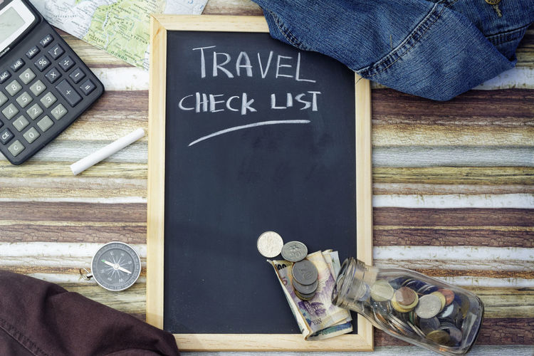 Travel plan concept Travel Vacation Plan Holidays Check List Checklist Tourism Money Glass Jar Concept Conceptual Compass Savings Dream Vacation Blackboard  Communication Directly Above High Angle View Text Close-up Chalk - Art Equipment