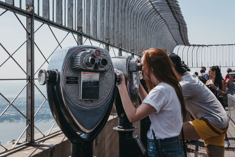Visitors using binoculars on the observation platform at Empire State Building, New York, USA. Tourism Travel United States USA New York City New York Real People Binoculars Visitors Observation Point Empire State Building Sightseeing Outdoors Young Adult People Travel Destinations Landmark Observation Deck Tourist Attraction  Lifestyles Millenials Vacations Holidays People Watching NYC Photography