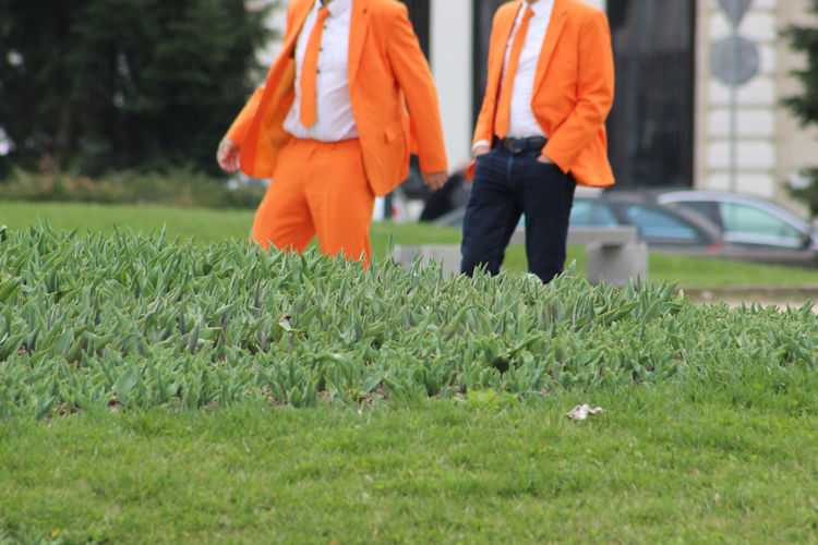 Midsection Of Businessmen Walking On Field