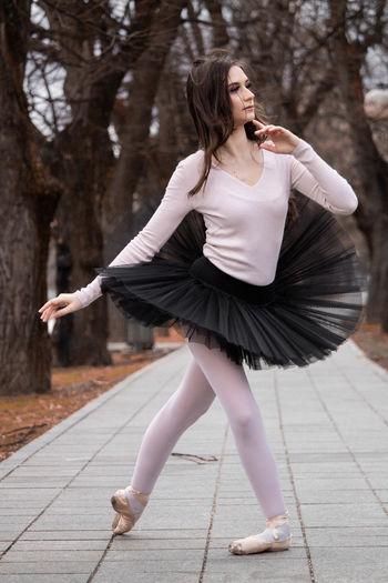 Ballerina dancing on footpath
