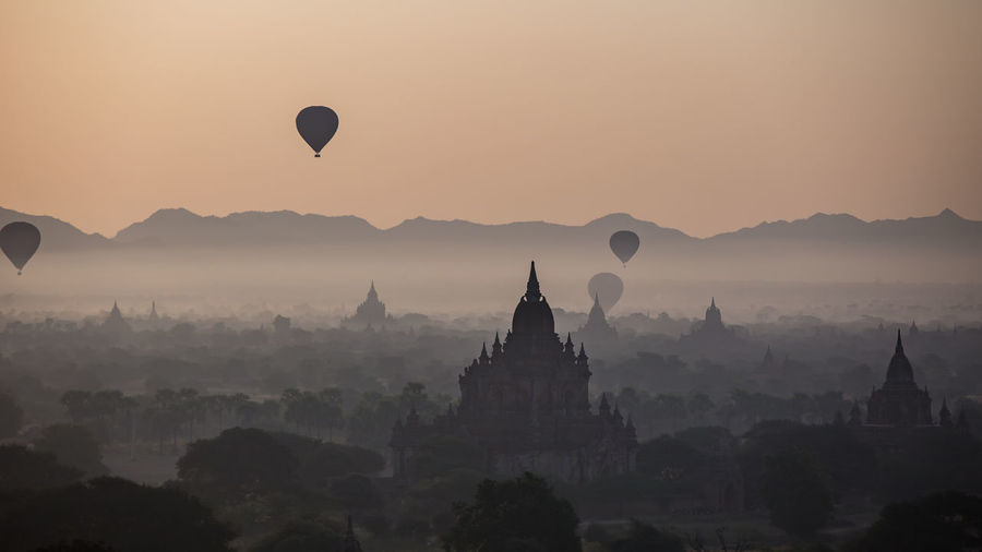 Hot air balloons against sky during sunset