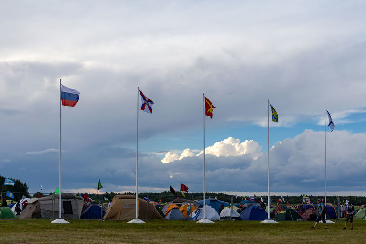 Group of people on flags at beach against sky