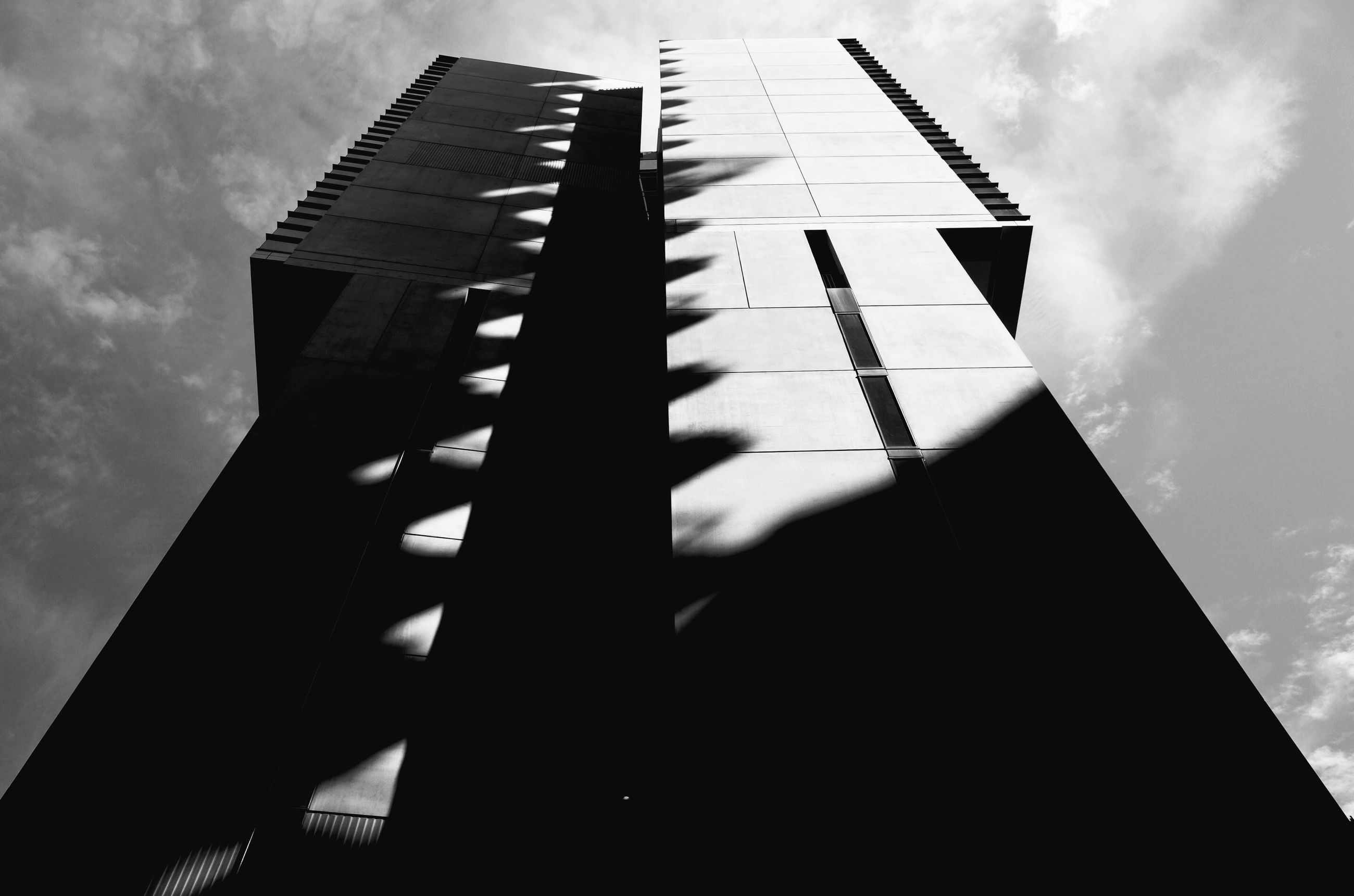 low angle view, architecture, built structure, building exterior, sky, tall - high, skyscraper, tower, tall, cloud - sky, city, modern, office building, no people, outdoors, day, cloud, building, silhouette, cloudy