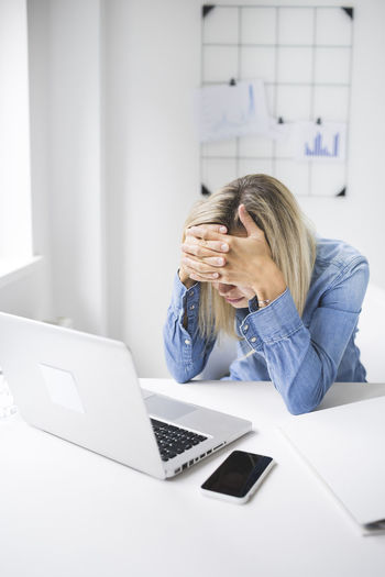 Frustrated businesswoman sitting at office