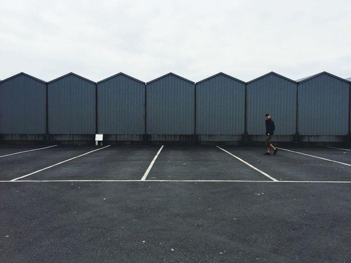 Side view of man walking in empty parking lot against sky