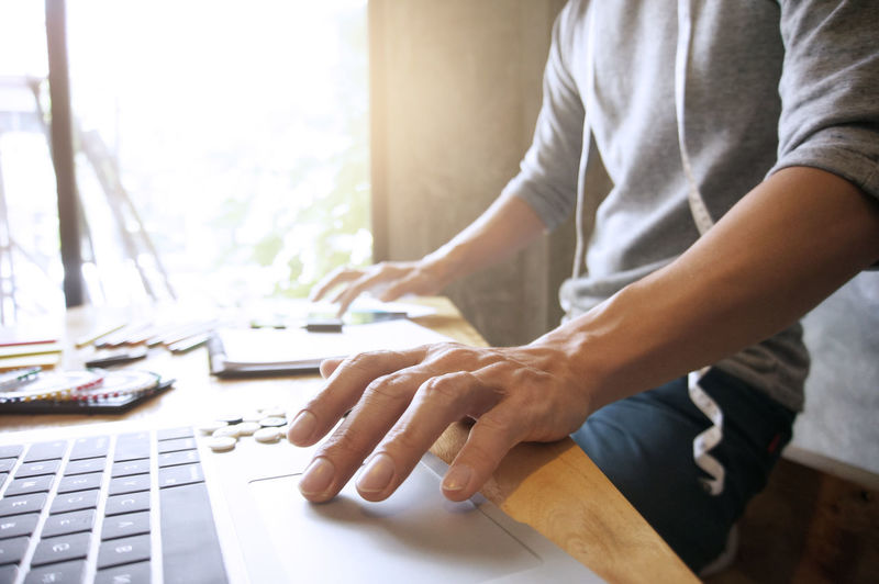 Midsection Of Fashion Designer Using Laptop In Office