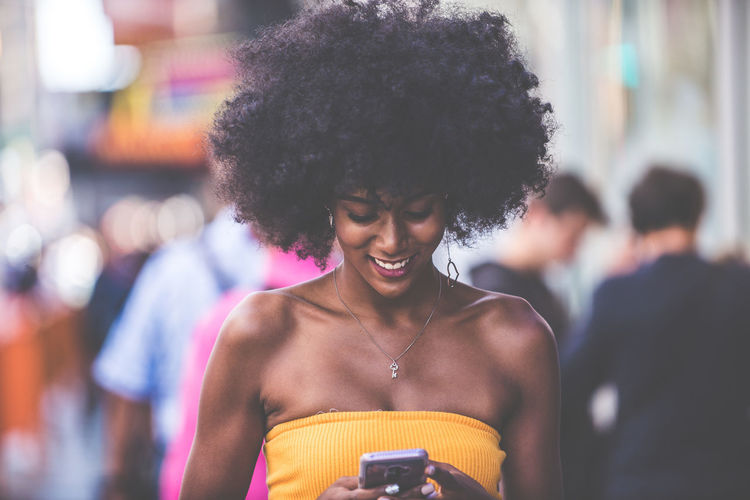 Happy young woman using smart phone on city street