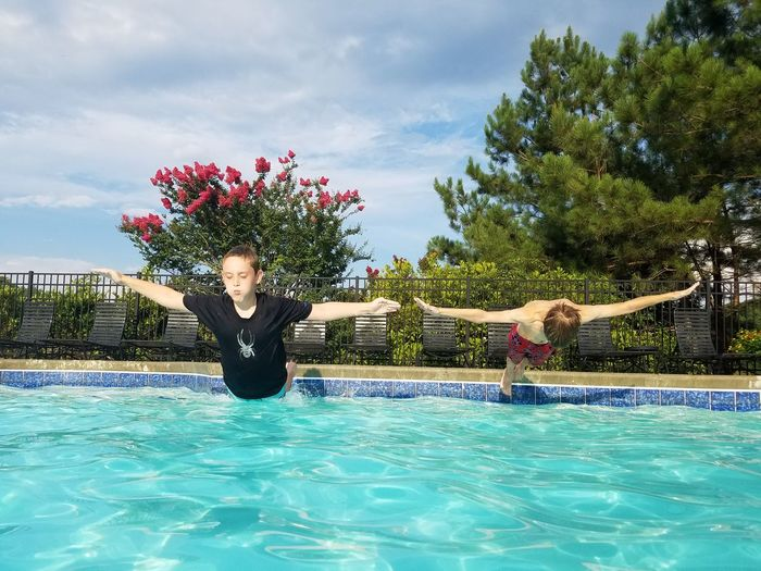 Boys with arms outstretched jumping in swimming pool