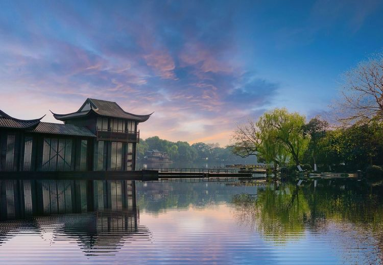 Built structure by lake against sky during sunset