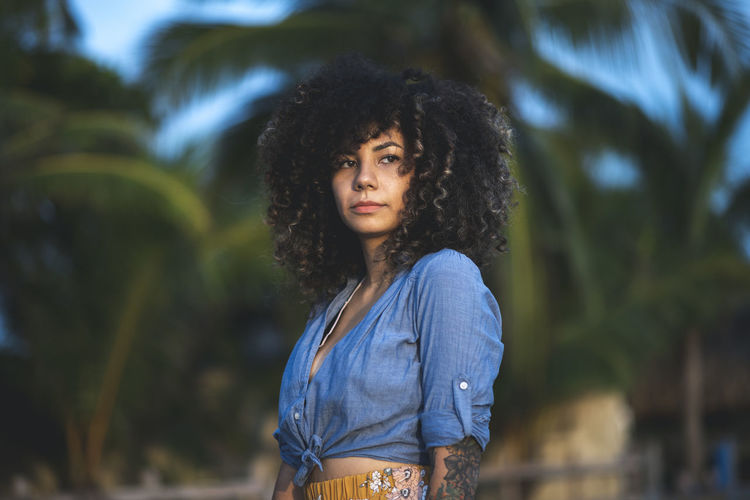 Curly haired woman looking away while standing at park