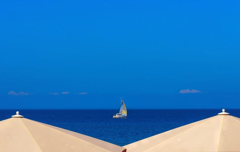 Sailboat Sailing On Sea Against Blue Sky
