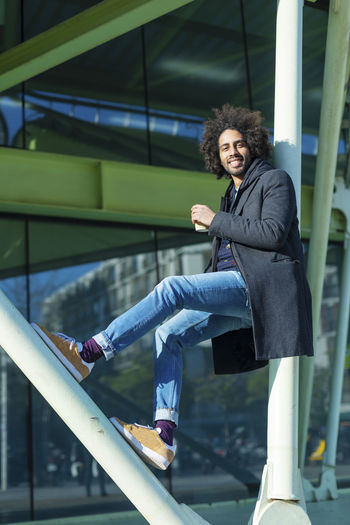 Portrait Of Young Man Sitting On Railing In City