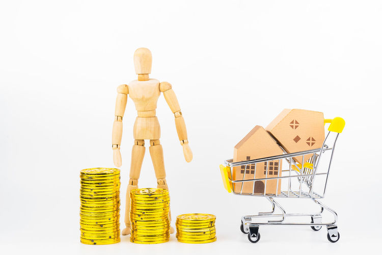 Wooden human mannequin holding shopping cart full of paper hose model, isolated on white background with copy space.Real estate concept, New house concept.Buying a house. Business Close-up Consumerism Container Copy Space Cut Out Figurine  Finance Human Representation Indoors  Male Likeness No People Representation Retail  Shopping Shopping Cart Small Still Life Studio Shot Toy Wheel White Background