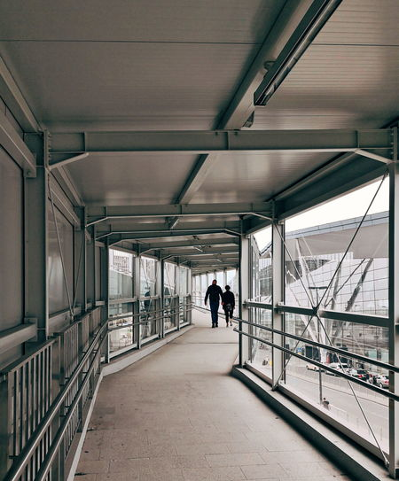 Rear View Of Couple Walking On Footbridge
