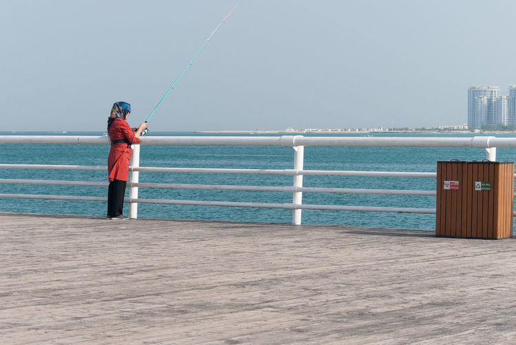 Iranian girl fishing Water Sea Sky One Person Standing Real People Leisure Activity Horizon Over Water Day Nature Horizon Beauty In Nature Casual Clothing Lifestyles Scenics - Nature Railing Outdoors Beach Iran Iranian Girl Fishing Kish Kish Island Persia Persian Gulf