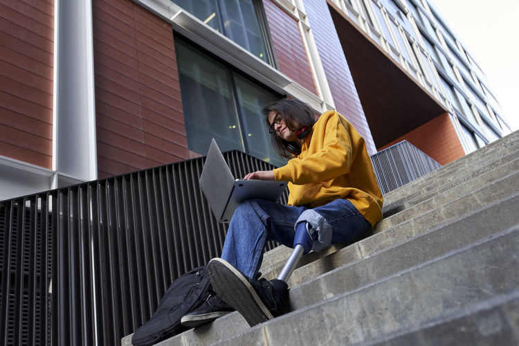 Low angle view of man sitting on staircase of building