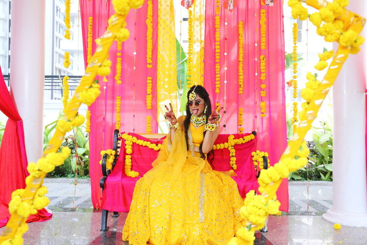 Portrait of bride wearing sunglasses gesturing while sitting on chair at haldi ceremony