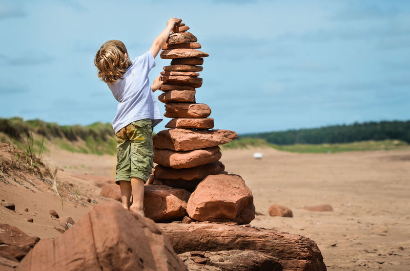 Rear view of boy stacking stones at field
