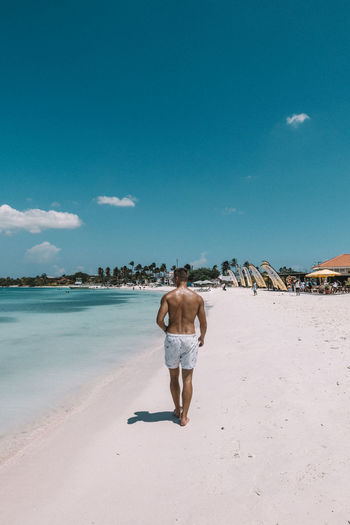 Rear view of shirtless man walking on shore at beach against blue sky
