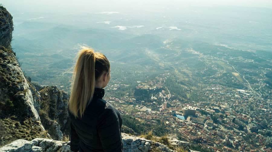 High angle view of woman looking at cityscape from mountain