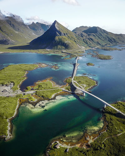 A drone shot of the Fredvang Bridges on the Lofoten. These crazy buildings are very important for the Lofoten as they are connecting all the different islands. They are extremely arched to allow bigger ships to pass them. My favorite part of this shot is the little house that is hiding at the bottom... can you spot it? Bird Eyes View DJI Mavic Pro Drone  From My Point Of View From Above  Norway Beauty In Nature Day Dji Dronephotography Green Color Lake Landscape Lofoten Mountain Mountain Range Nature No People Outdoors Scenics Sky Svolvær Tranquil Scene Tranquility Water