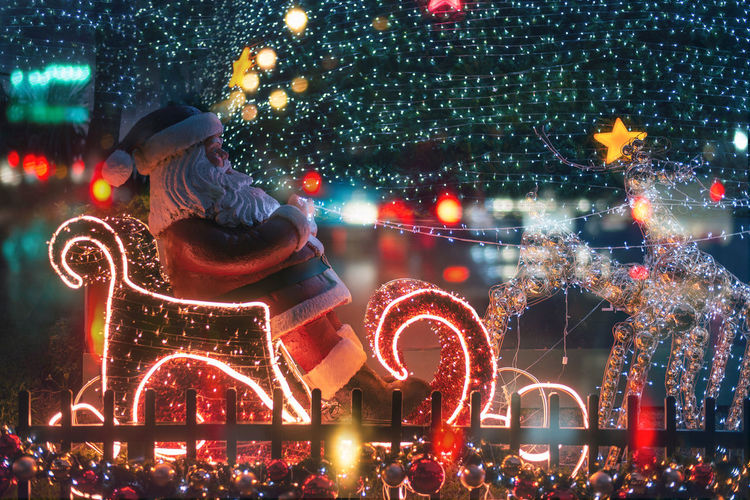 Illuminated christmas lights in city at night