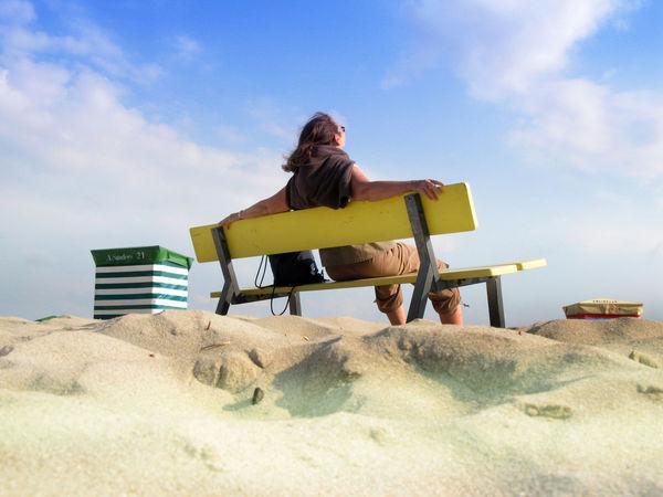 Frau sitzt auf Holzbank in den Dünen und entspannt Blauer Himmel Dünen Entspannen Entspannung Frau Sand Strandhäuser Strandkörbe Urlaub Weiße Wolken Wohlfühlen