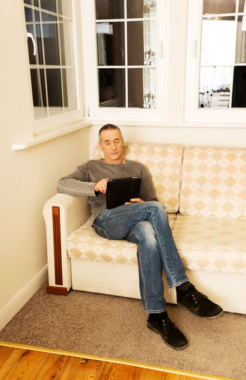Full Length Of Mature Man Using Digital Tablet While Sitting On Sofa At Home
