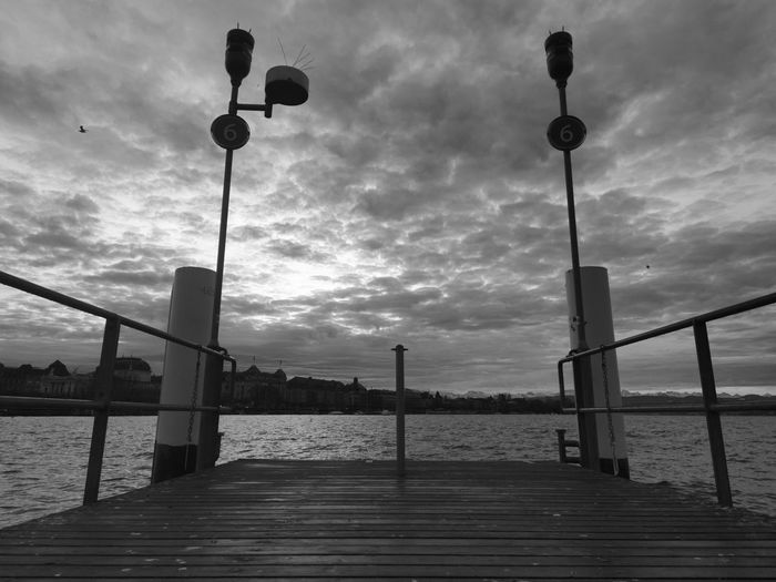 Street lights on pier by sea against sky
