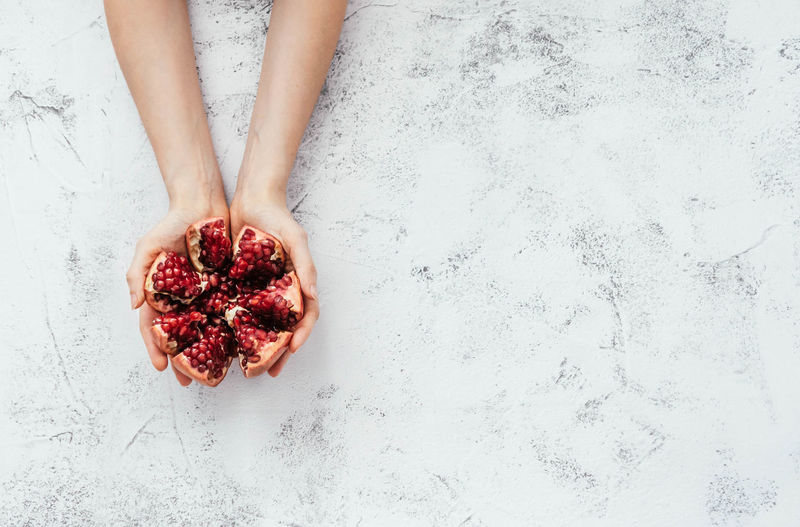 Directly above shot of hand holding strawberry