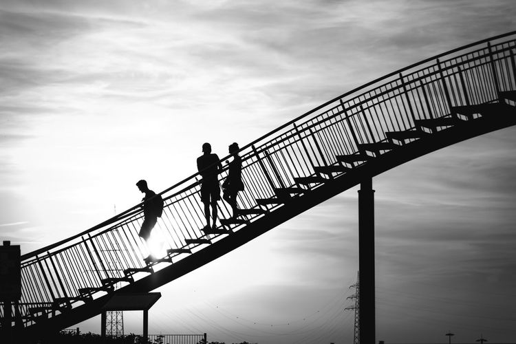 Low Angle View Of Silhouette People Walking On Stairs Against Sky