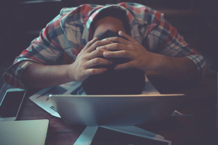 High angle view of stressed man by desktop pc