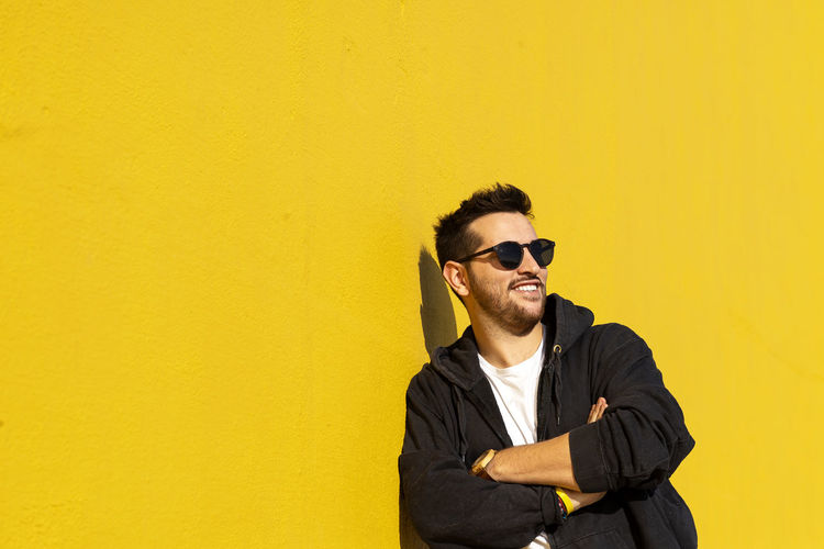 Young man wearing sunglasses standing against yellow wall