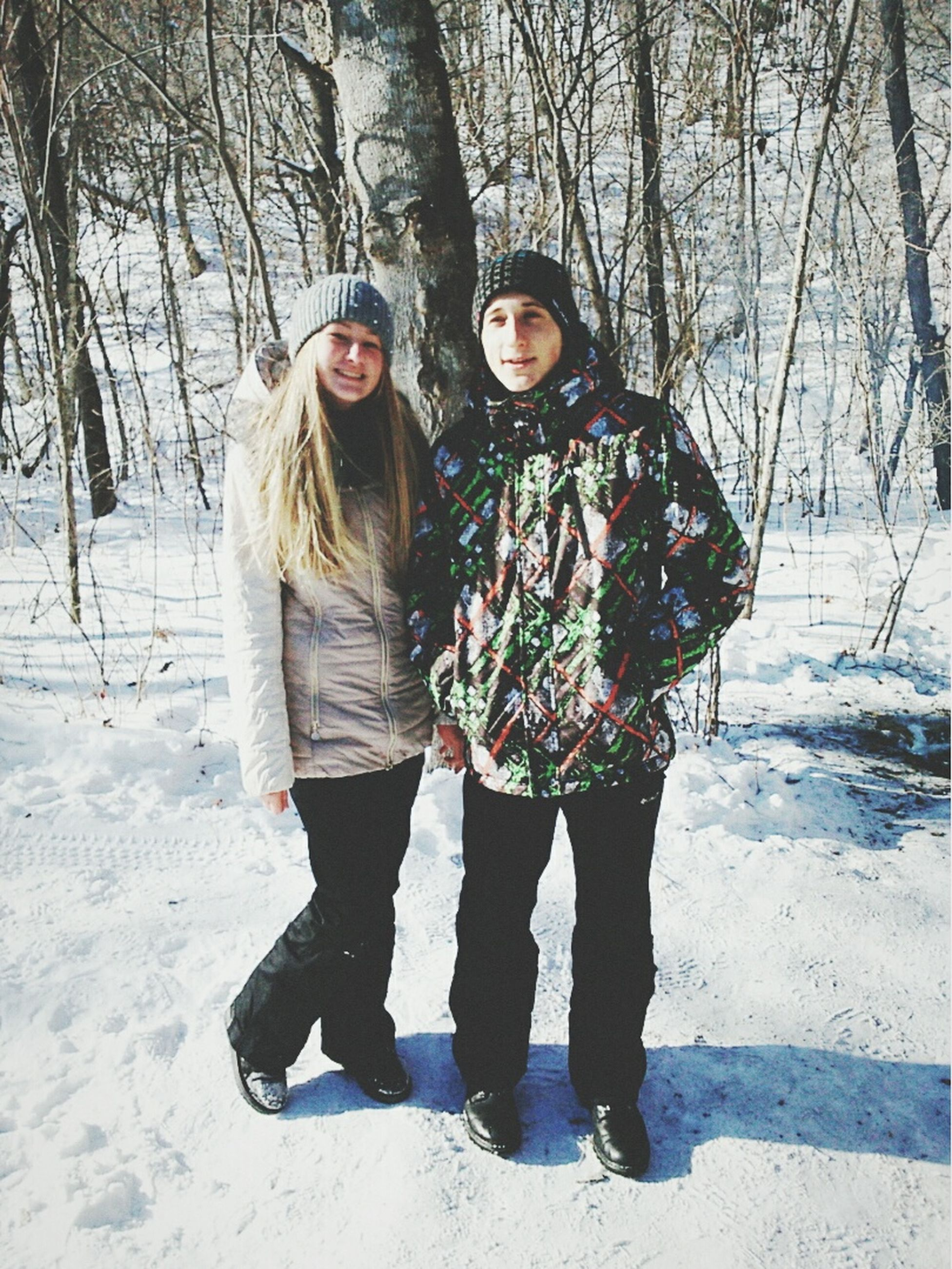 winter, lifestyles, leisure activity, snow, cold temperature, person, full length, season, looking at camera, casual clothing, front view, portrait, warm clothing, standing, young women, young adult, tree, smiling