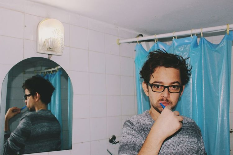 Portrait of young man with reflection on wall