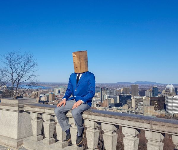 Man Covered With Paper Bag Sitting On Railing Against Clear Blue Sky