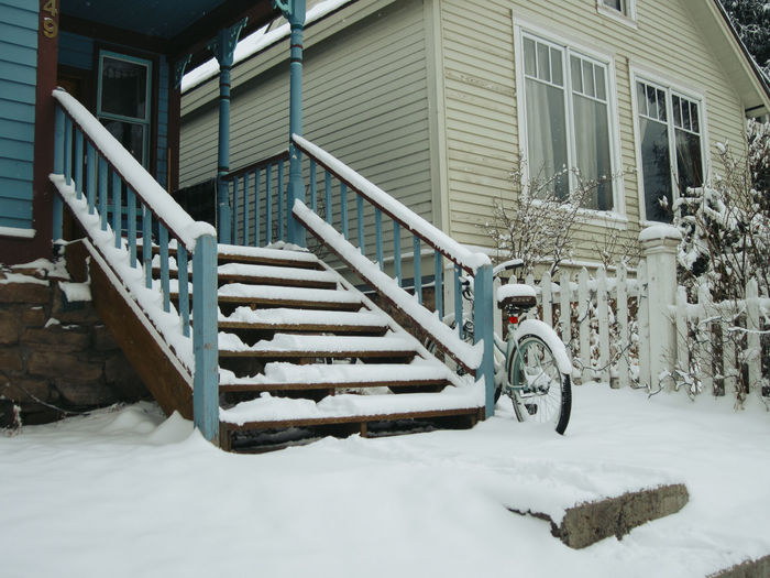 Bicycle parked on staircase of building during winter