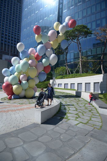 Architecture Balloon Building Building Exterior Built Structure City City Life Day Footpath Helium Balloon Incidental People Multi Colored Nature Outdoors People Plant Real People Street Walking Women