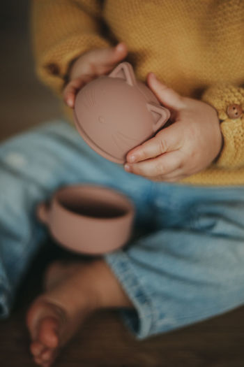 Midsection of boy holding coffee while sitting on table